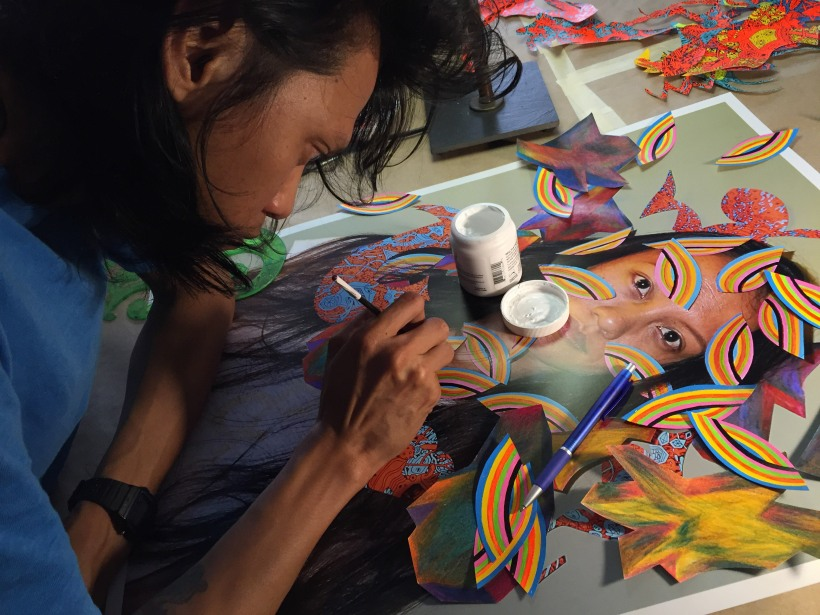 Dex Fernandez paints a photograph of close friend Ida Calumpang, at his Midtown apartment, on 08/17/15. Some of the cutouts were stuck on her face during the shoot.