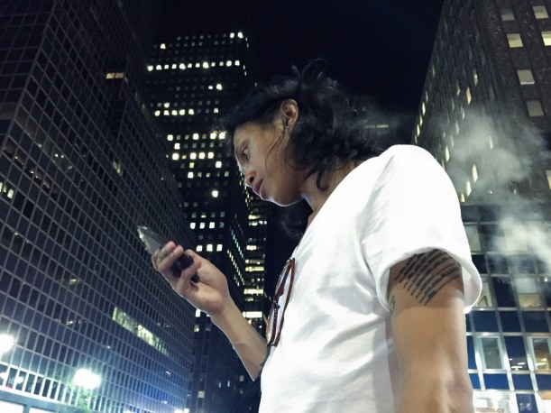 Dex Fernandez walks home from Grand Central Station, after a fun night, on 08/16/15. Eyes locked on his phone, as always...